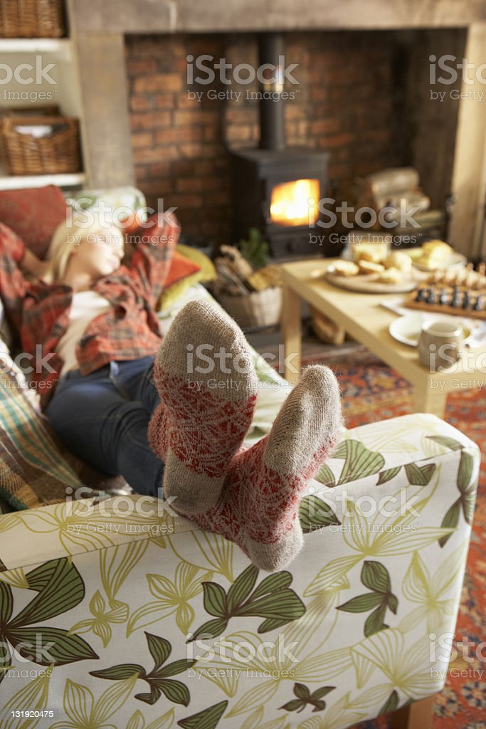 Yong woman relaxing by fire in a house stock photo