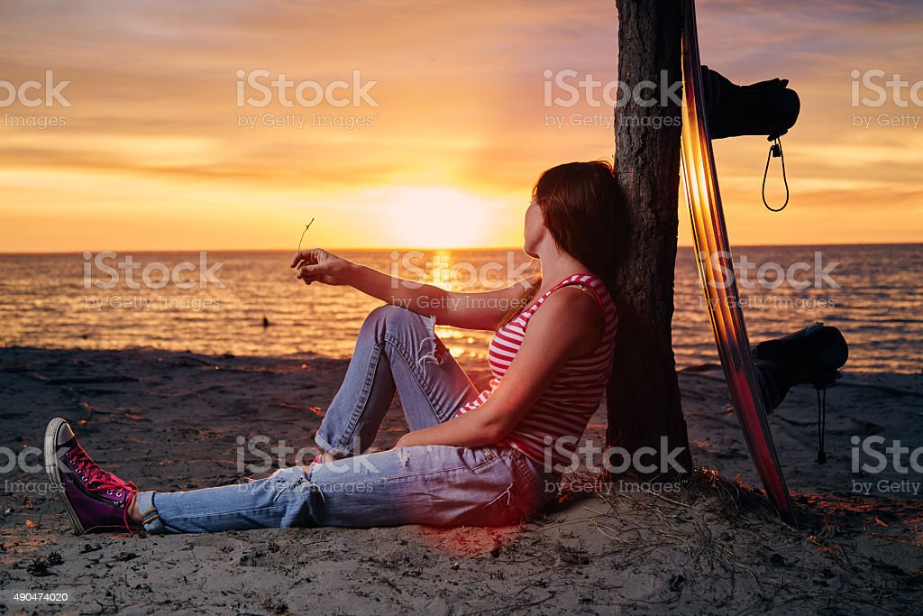 Yong woman sitting on the shore with wakeboard stock photo