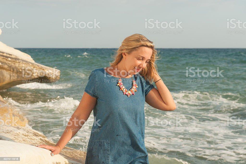 Yong woman walkin on t he rocks at the seaside stock photo