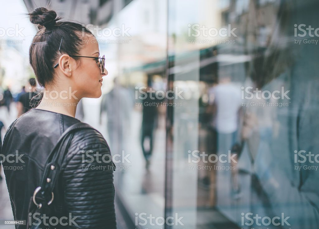 yooung woman looking at shop windows stock photo