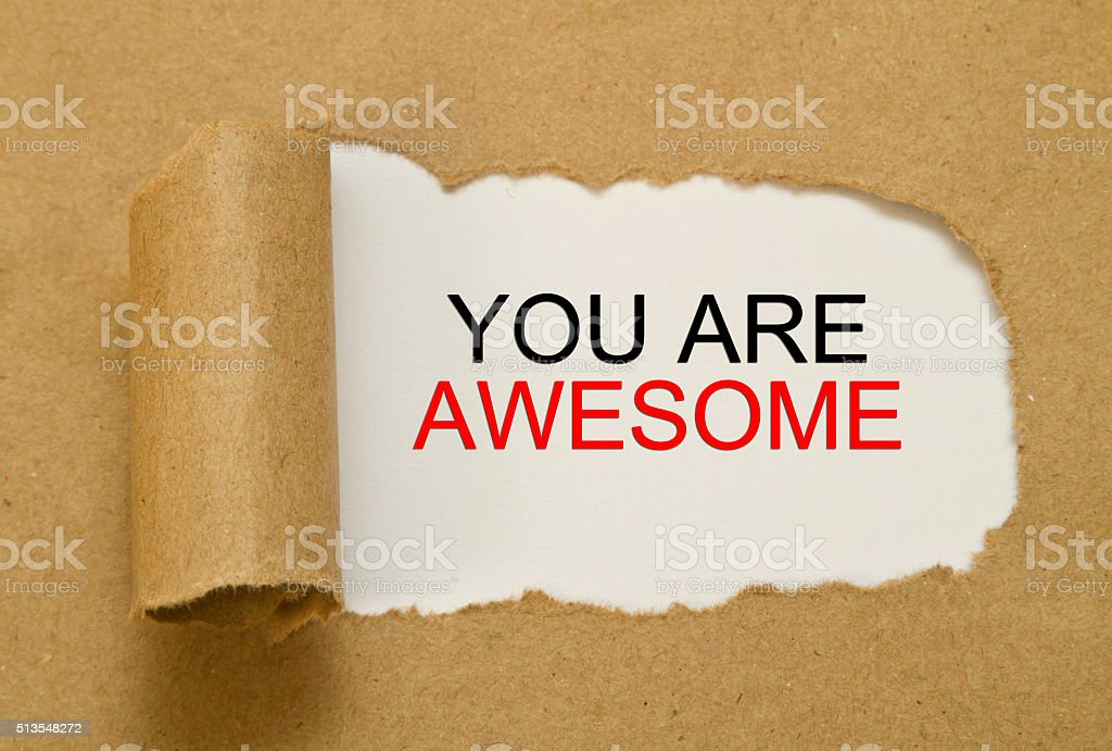 You are awesome message written under torn paper stock photo