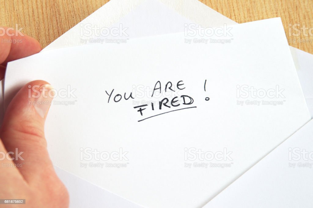 You Are Fired, hand holding employment termination letter, white envelope, wooden background stock photo