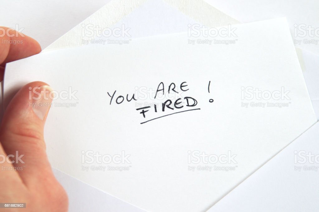 You Are Fired, hand holding employment termination letter, white envelope stock photo