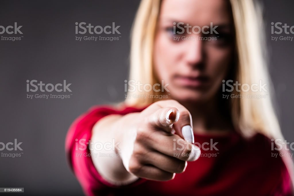 you finger shown by a blonde blurred woman stock photo