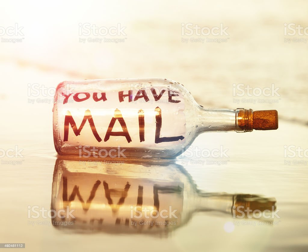 'you have mail' says message in bottle on beach stock photo