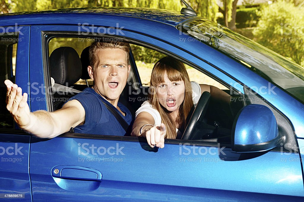 You roadhog! Young couple in car gesture angrily at someone stock photo