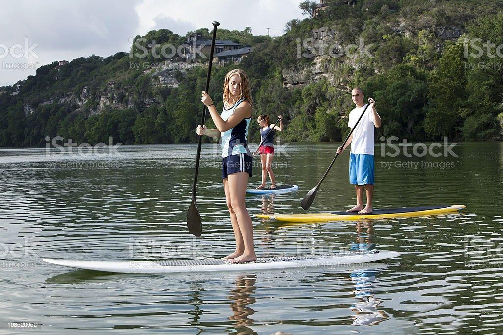 Youg adults paddleboarding stand up paddling stock photo