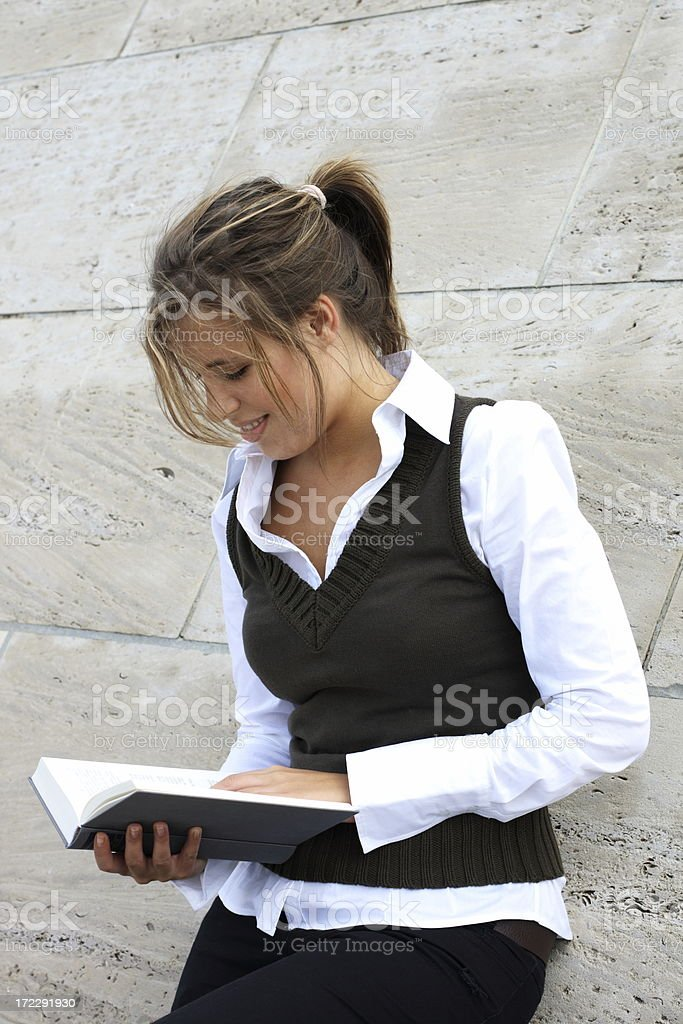 Youn female student reading a hardcover book stock photo