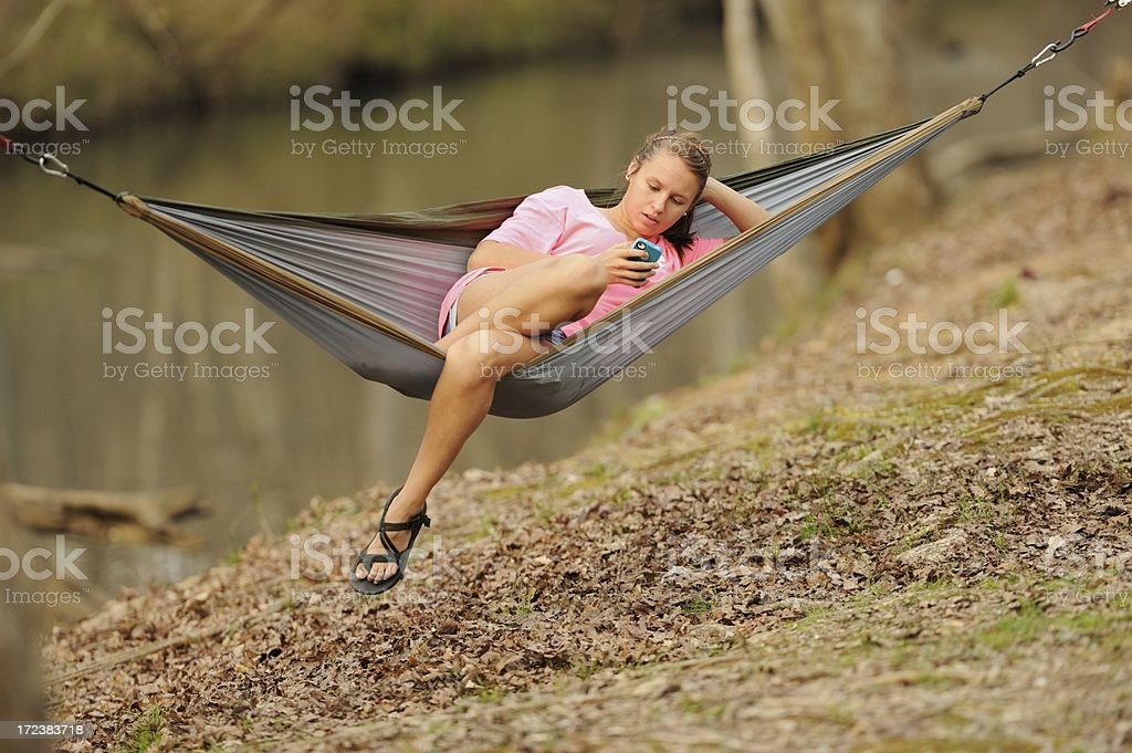 Youn girl resting in hammock using cell phone royalty-free stock photo