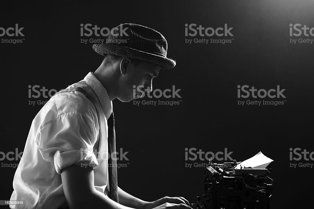 Young 1920s Reporter Writing Headline Story on Typewriter stock photo