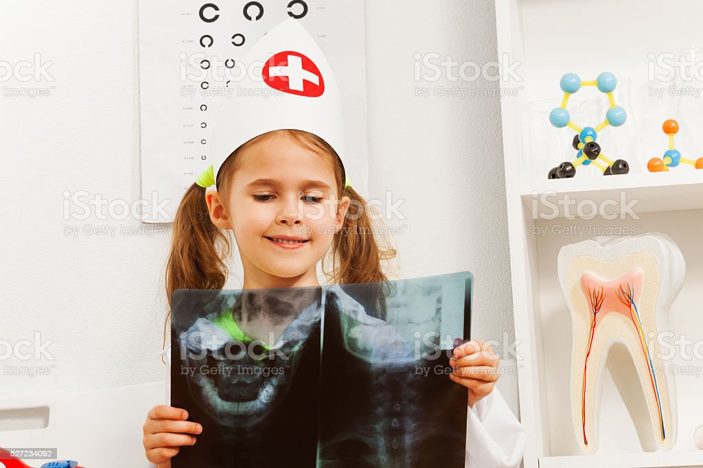 Young 5 years old dentist studying a skull x-ray stock photo