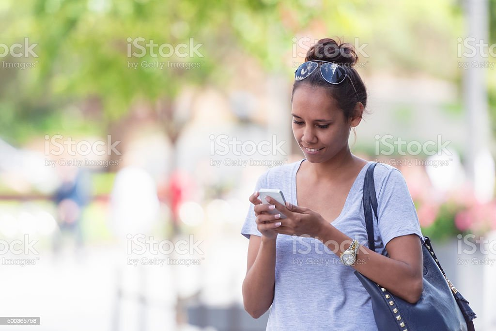 Young Aboriginal woman texting stock photo