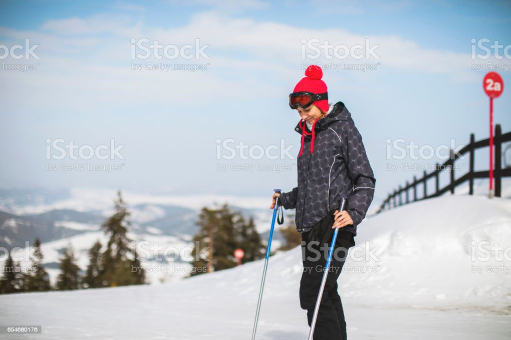 Young active woman skiing in the mountains stock photo