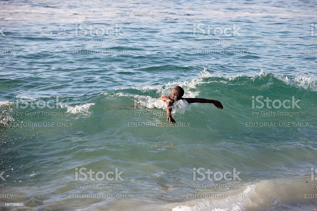 Young adult african male riding the waves royalty-free stock photo