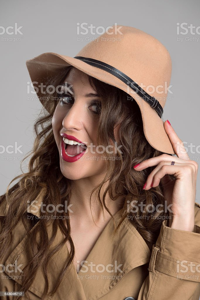 Young adult beautiful woman posing at camera holding her hat stock photo