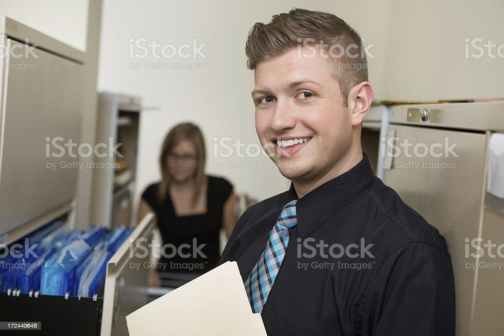Young adult businessman working in file room of office royalty-free stock photo