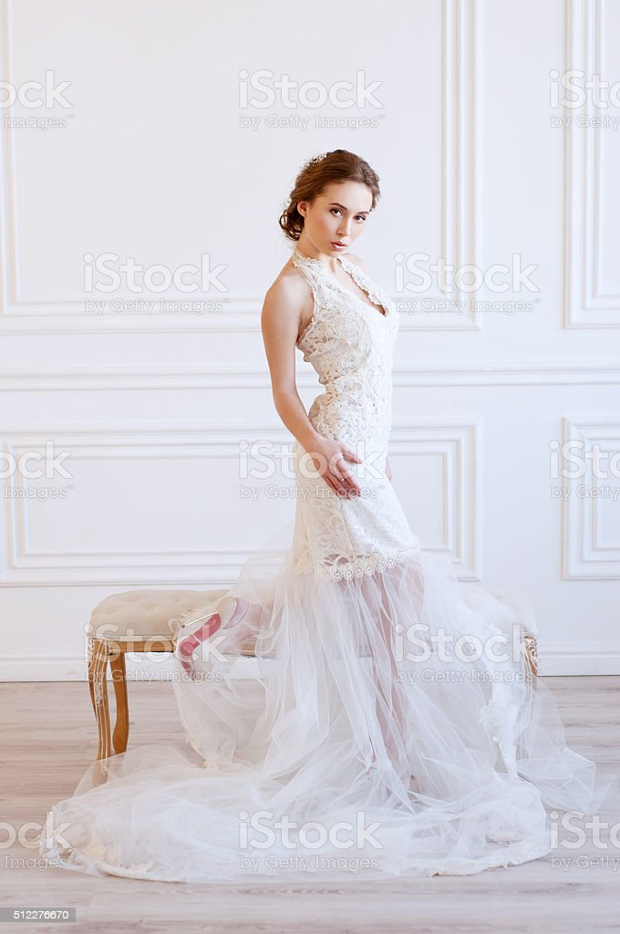 Young adult caucasian bride demonstrating a white bridal gown stock photo