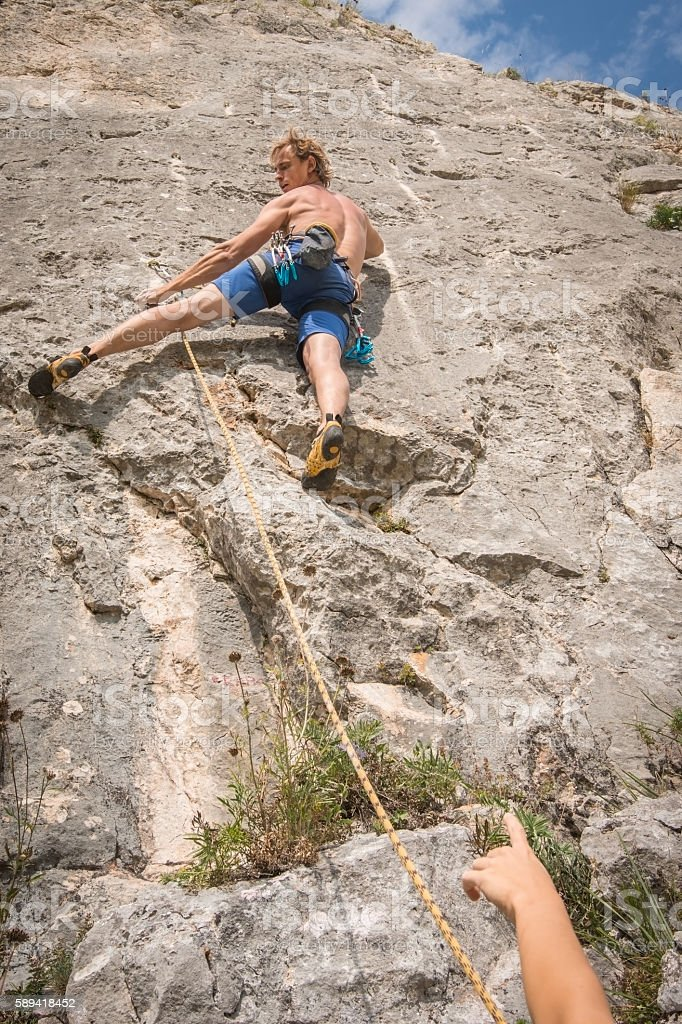 Young adult climbing rock secured in rope stock photo