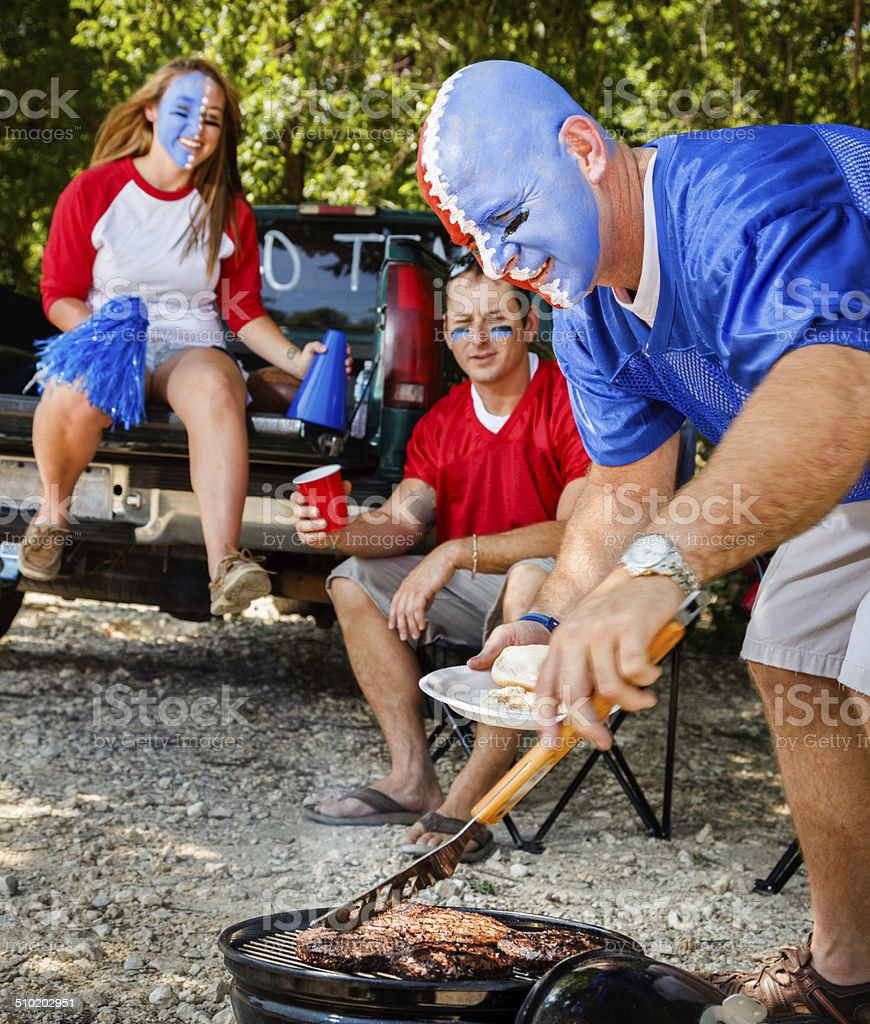 Young Adult College Football Fans Tailgating with barbeque grilled food stock photo