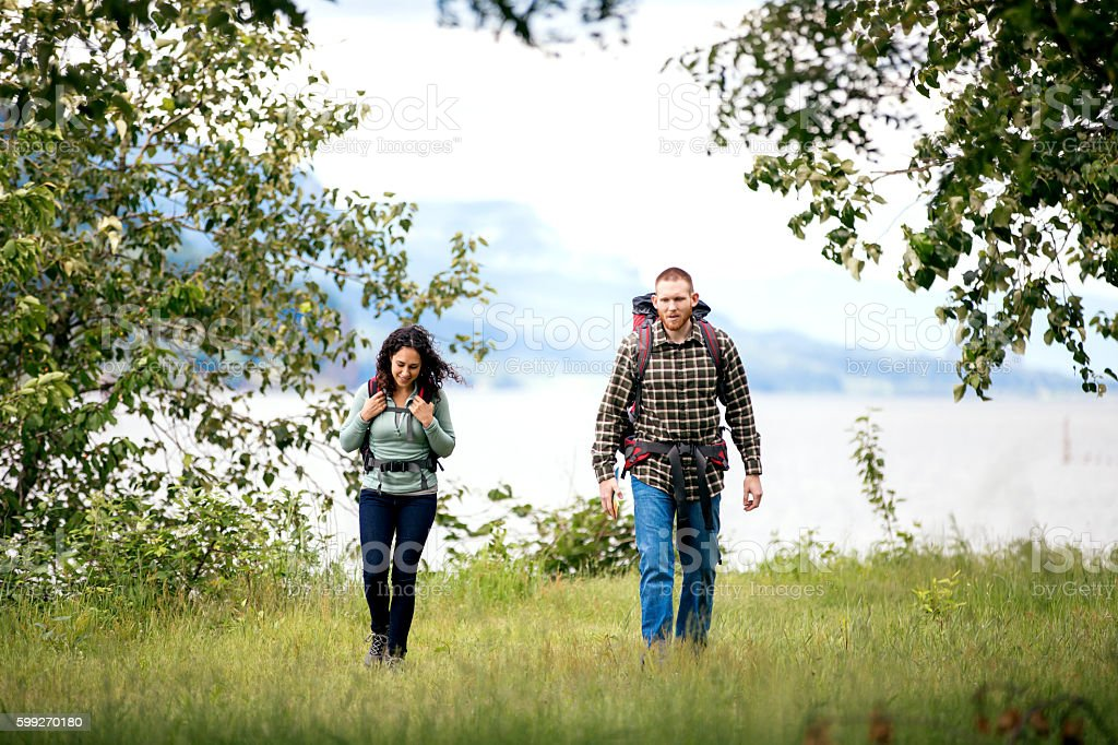 Young adult couple hiking through the forest stock photo