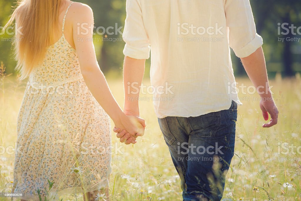 Young adult couple holding hands walking on grass stock photo