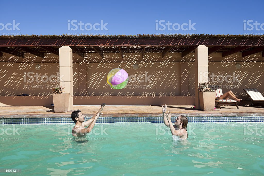 Young Adult Couple Playing With Beach Ball In Swimming Pool royalty-free stock photo