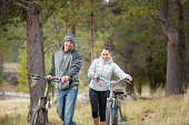 Young adult couple riding bikes outdoors in nature