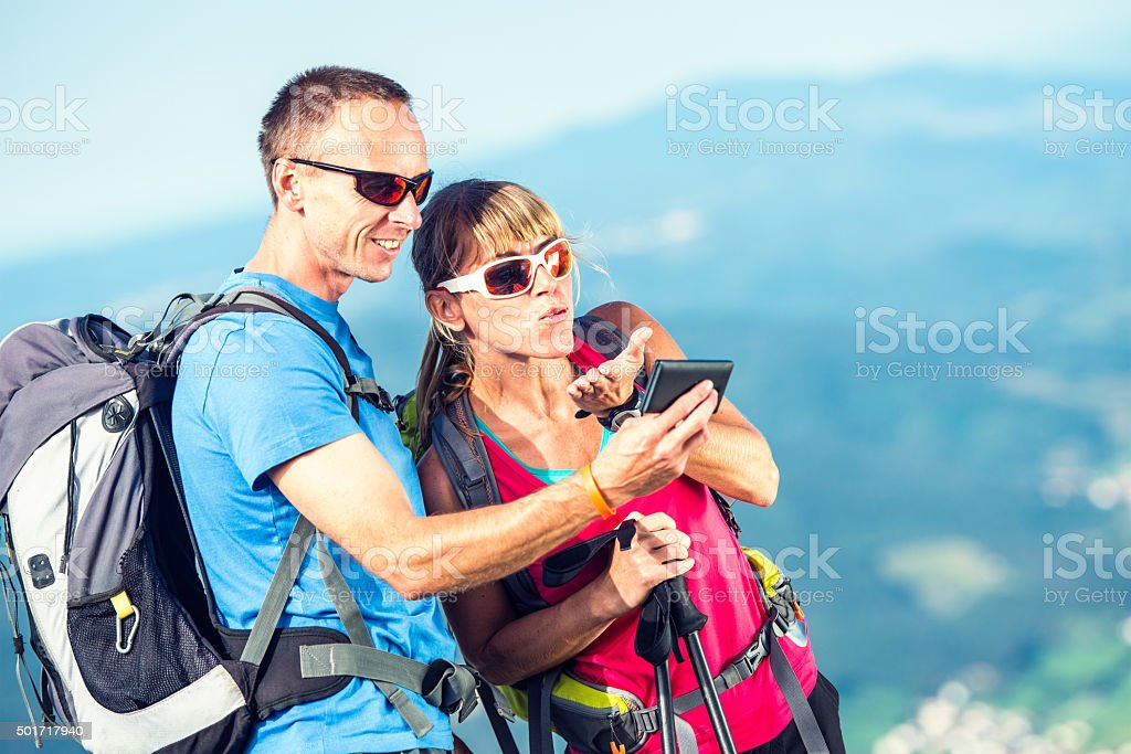 Young adult couple taking selfie on top of a mountain stock photo