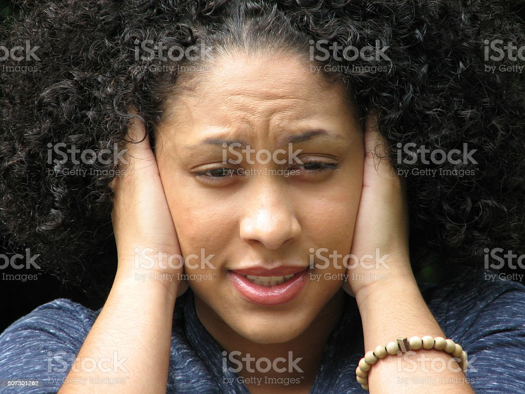Young adult covering ears stock photo