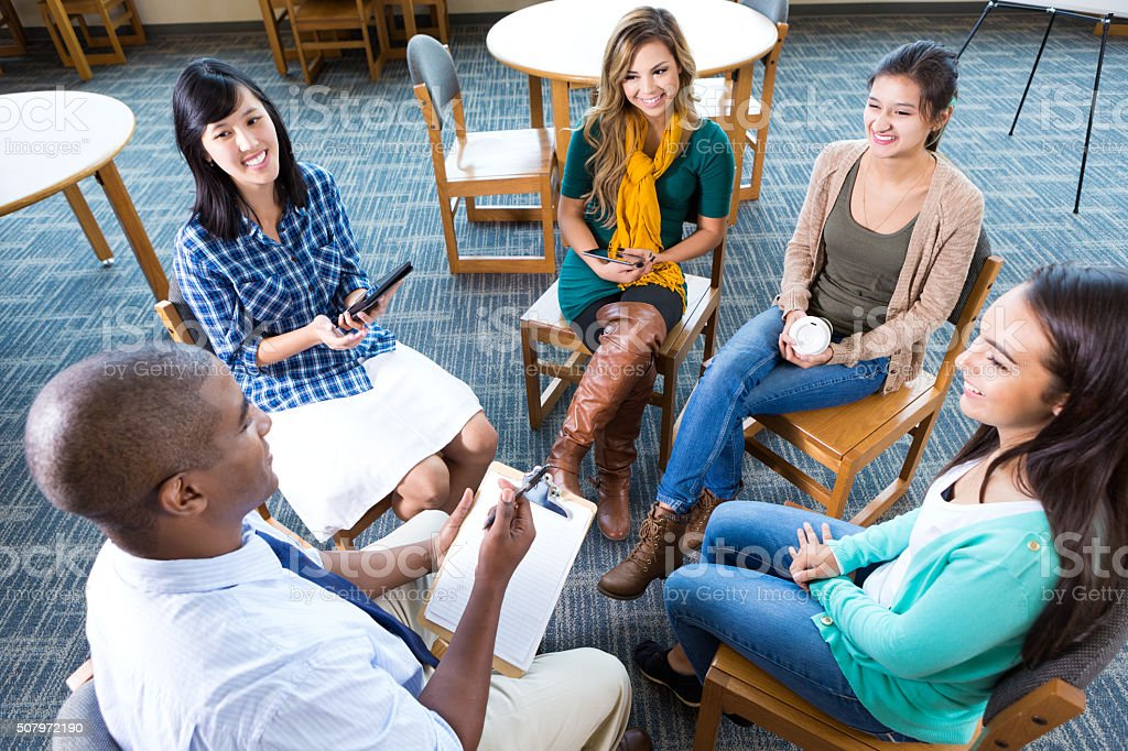 Young adult creative professionals discuss project in group stock photo