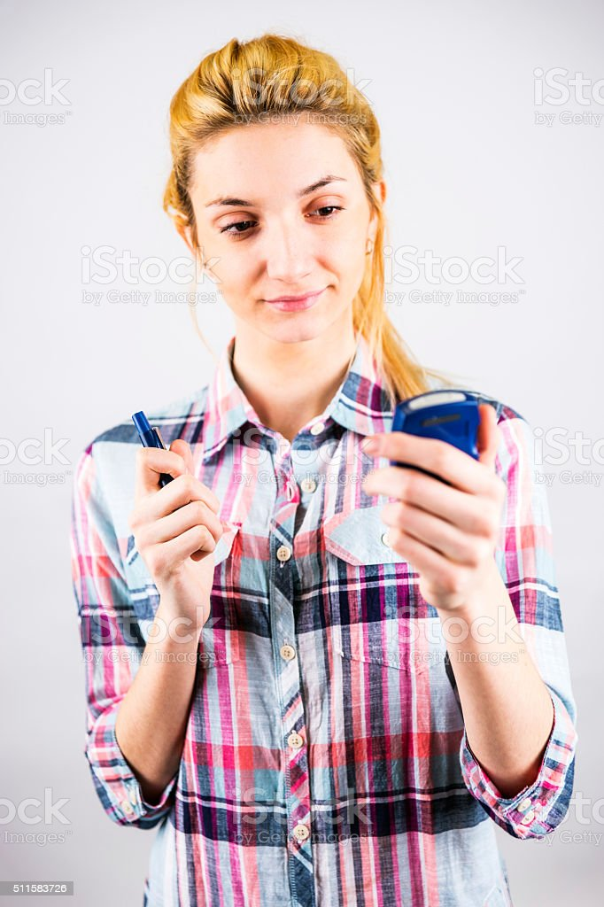 Young adult diabetes patient checking her blood sugar stock photo
