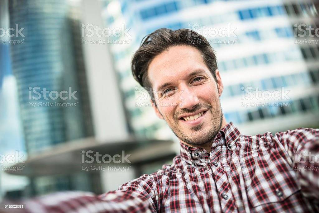 young adult entrepreneur doing a selfie on the city stock photo