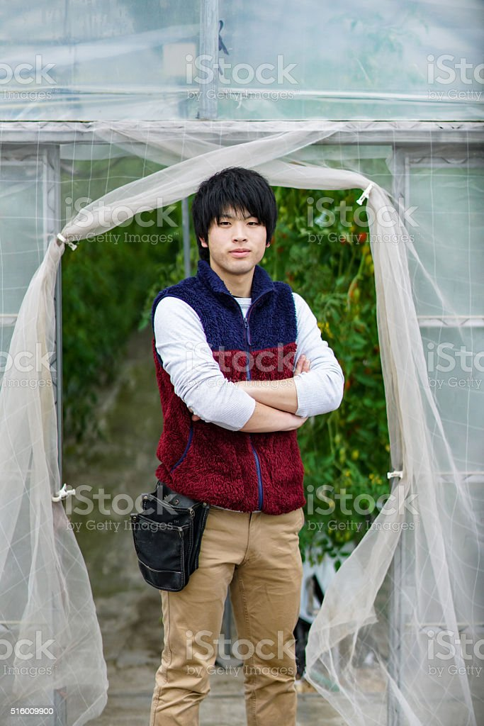 Young adult entrepreneur standing in his small business greenhouse stock photo