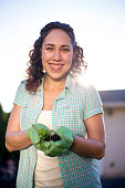 Young adult ethnic female holding small plant in gloved hands