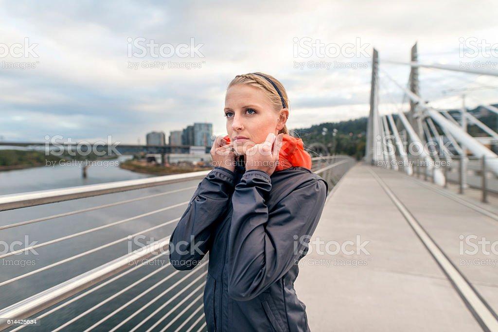 Young adult female athlete pulling jacket around her neck stock photo