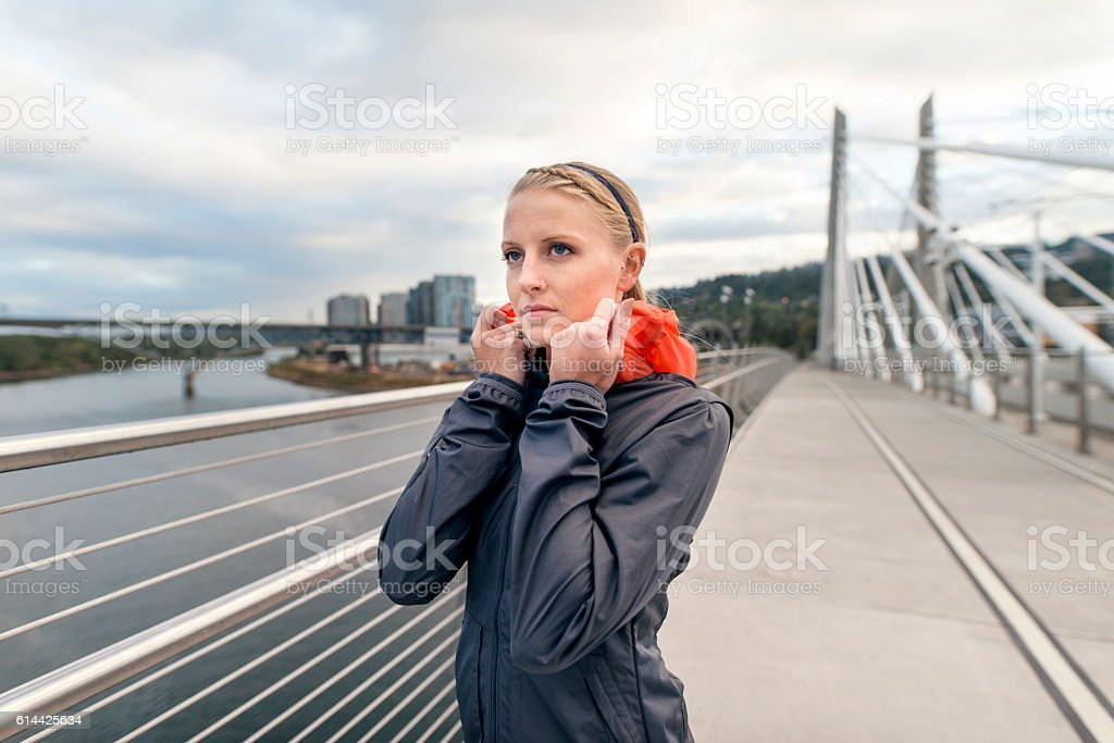 Young adult female athlete pulling jacket around her neck stock photo
