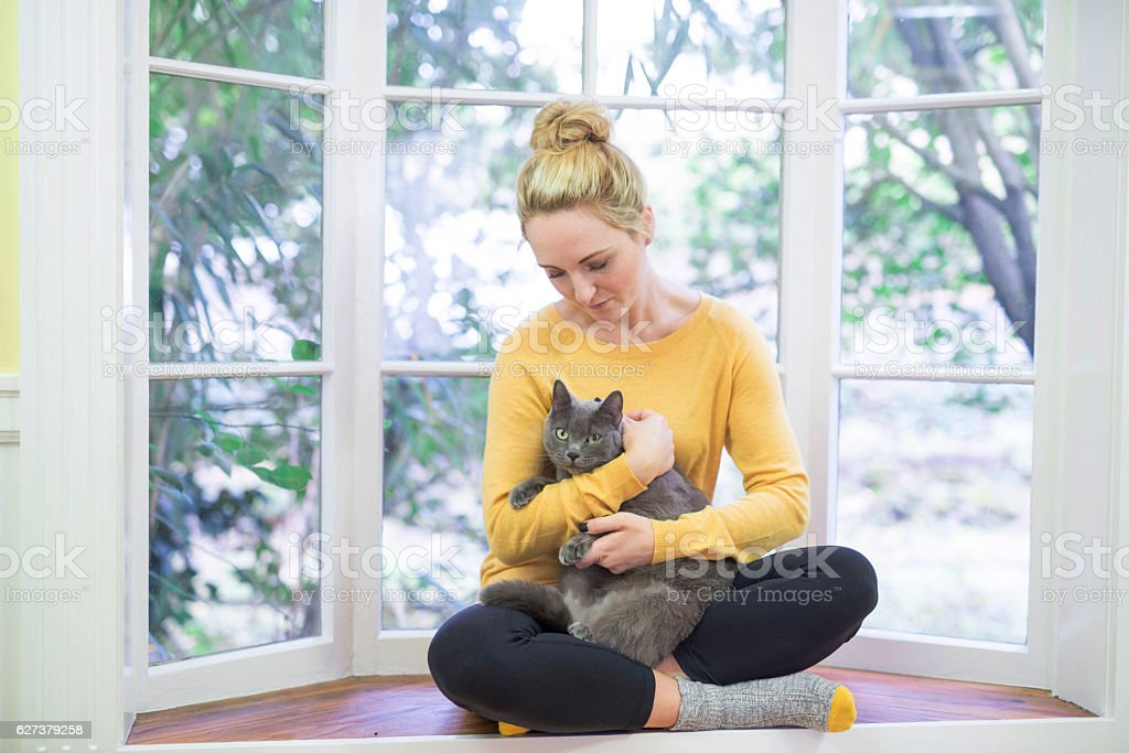 Young adult female craddling her cat in a reading nook stock photo