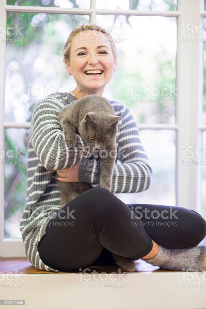 Young adult female laughing while holding her kitty stock photo