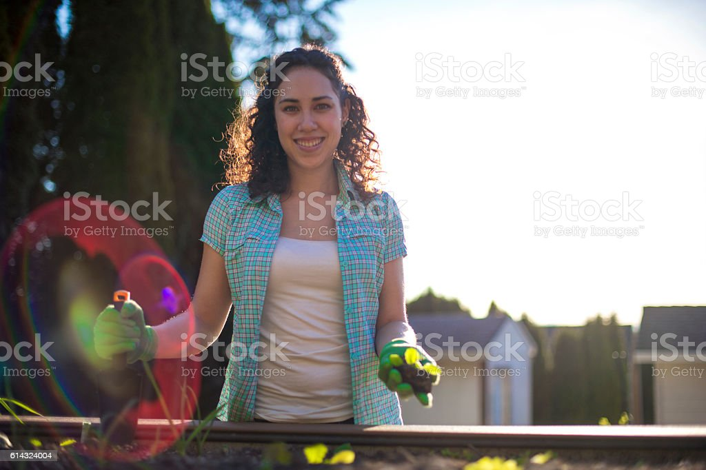 Young adult female ready to plant in her garden stock photo