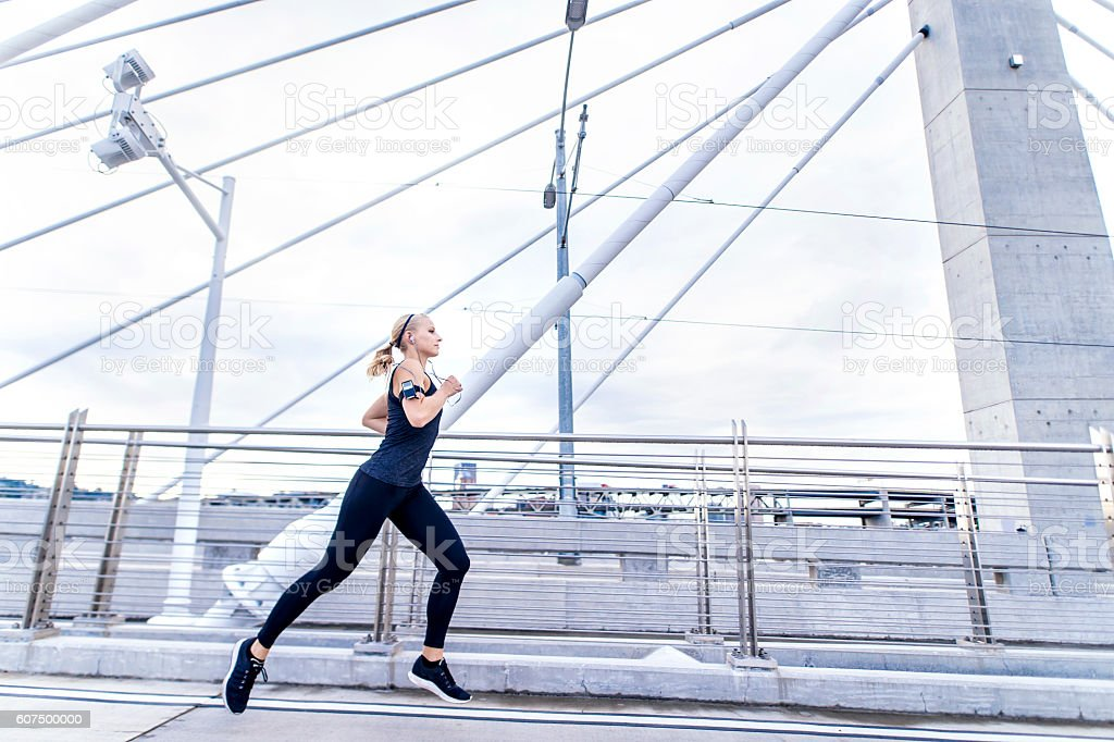 Young adult female running across a bridge in an urban stock photo