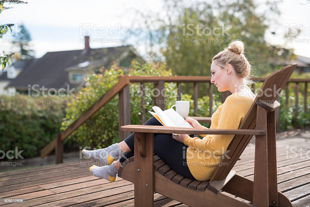 Young adult female sitting on porch drinking tea and reading stock photo