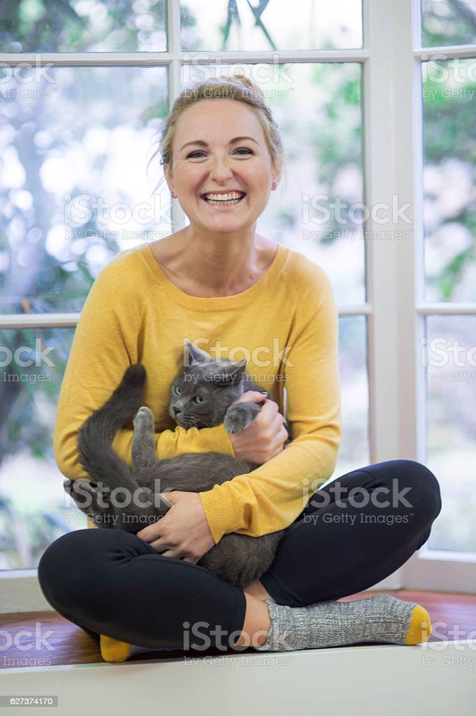 Young adult female smiling and holding her grey cat stock photo