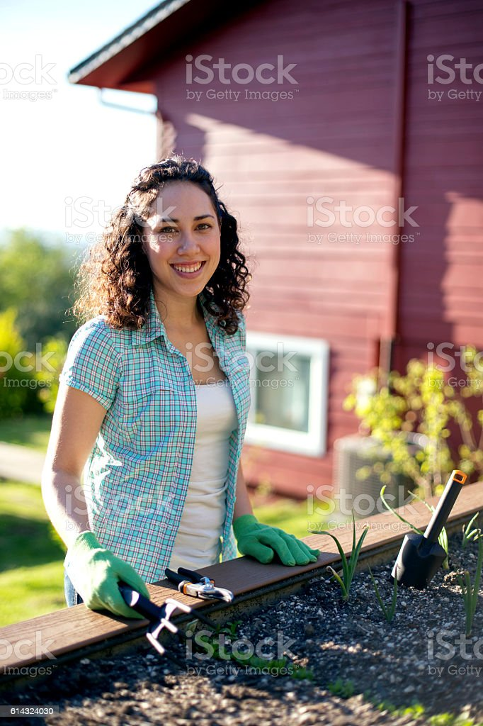 Young adult female smiling next to her garden bed stock photo