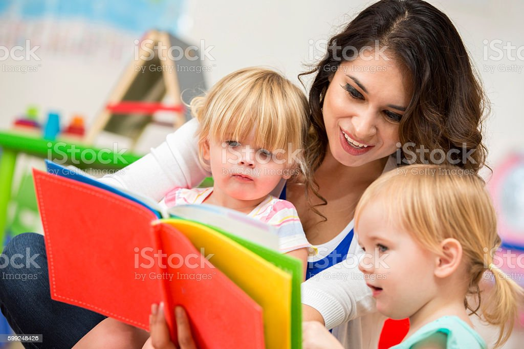 Young adult female teacher reading a book to two preschoolers stock photo