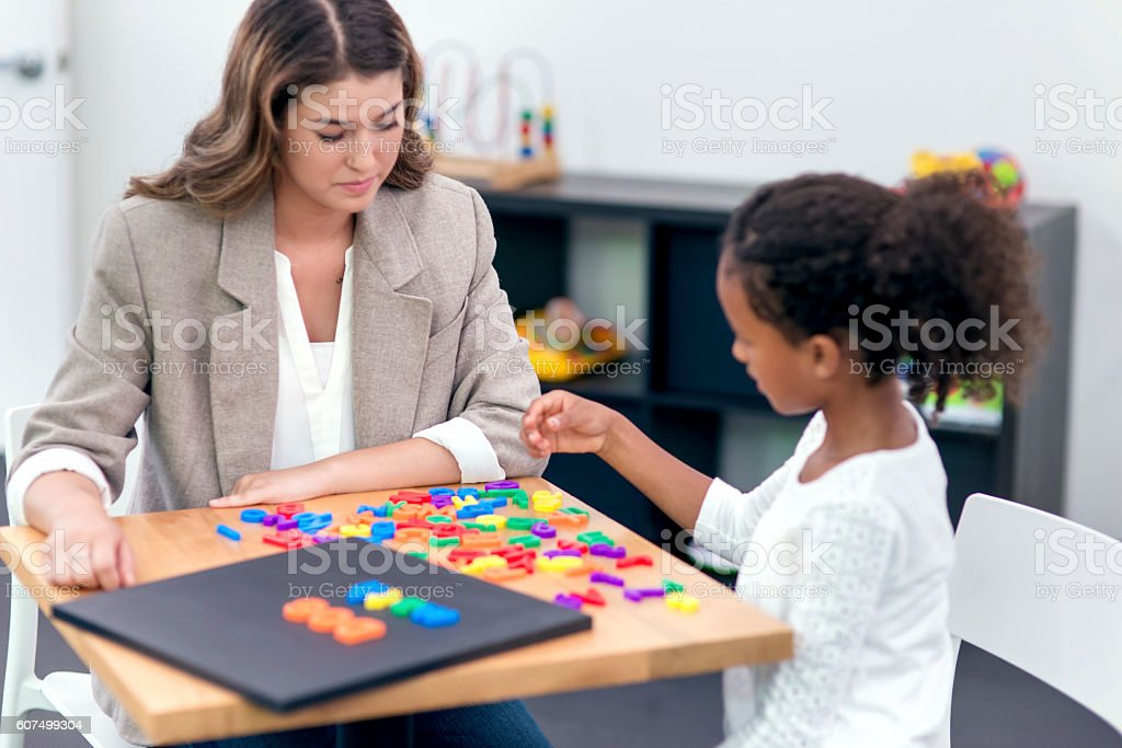 Young adult female therapist assisting a young patient in therapy stock photo