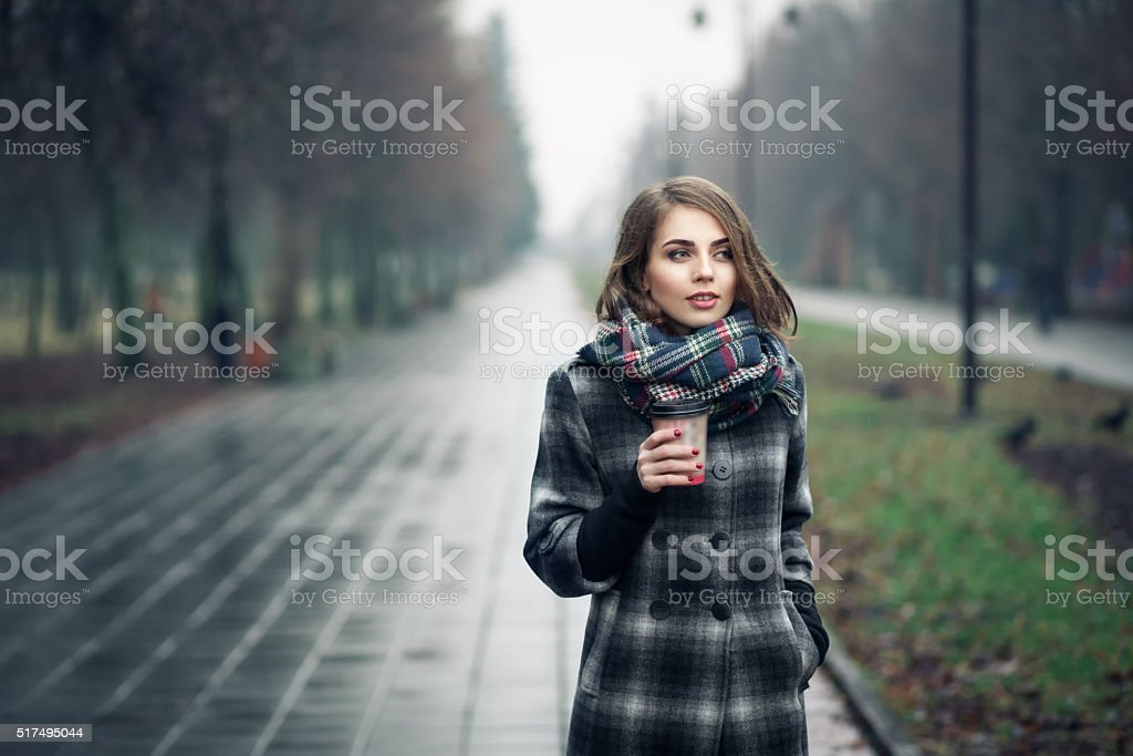 young adult female with cup of coffee in city park; stock photo