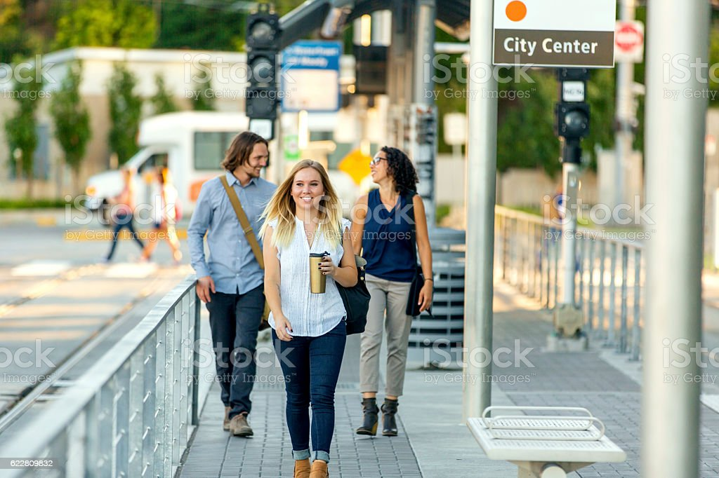 Young adult female working professional drinking coffee and walking stock photo