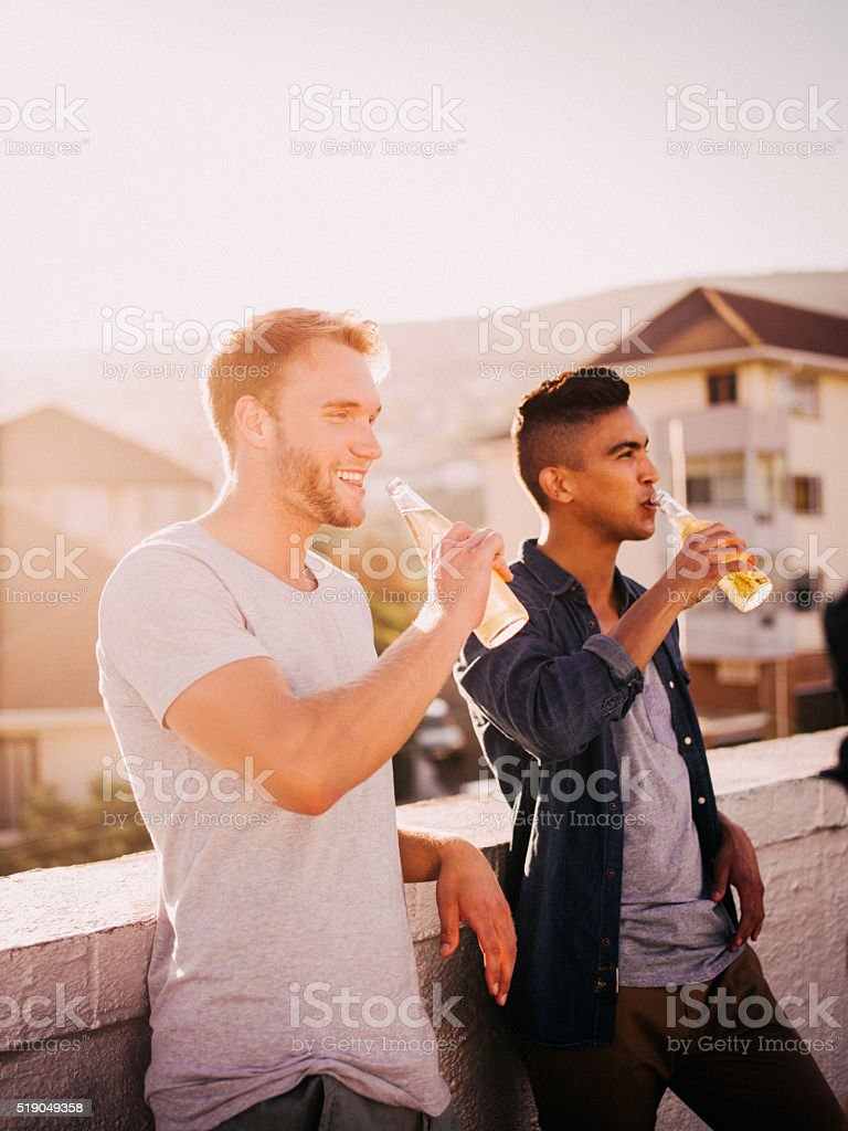 Young adult friends hanging out for a drink on rooftop stock photo