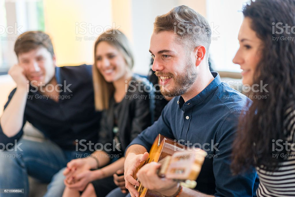 Young adult friends having fun in living room stock photo