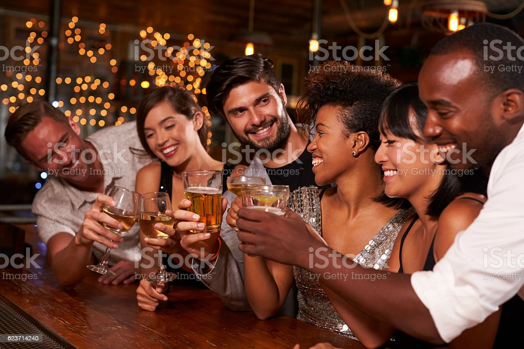 Young adult friends making a toast by the bar at a stock photo